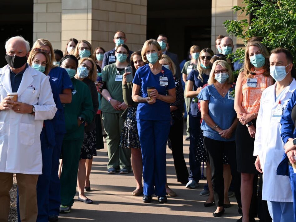 Front-line workers at a medical center in Aurora, Colo., gather for a COVID-19 memorial on July 15 to commemorate the lives lost in the coronavirus pandemic. New estimates say many thousands more will die in the U.S. this summer and fall. (Hyoung Chang/MediaNews Group/Denver Post via Getty Images)