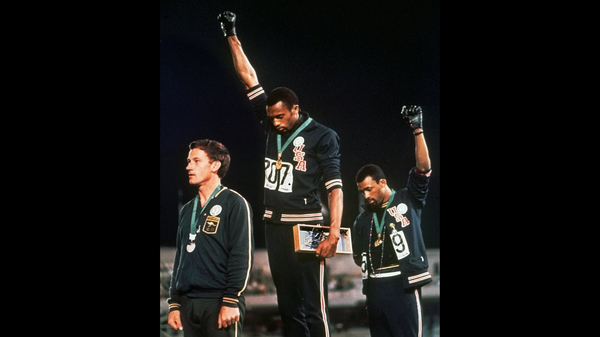 In this Oct. 16, 1968, photo, U.S. athletes Tommie Smith, center, and John Carlos raise their gloved fists after Smith received the gold and Carlos the bronze for the 200 meter run at the Summer Olympic Games in Mexico City.