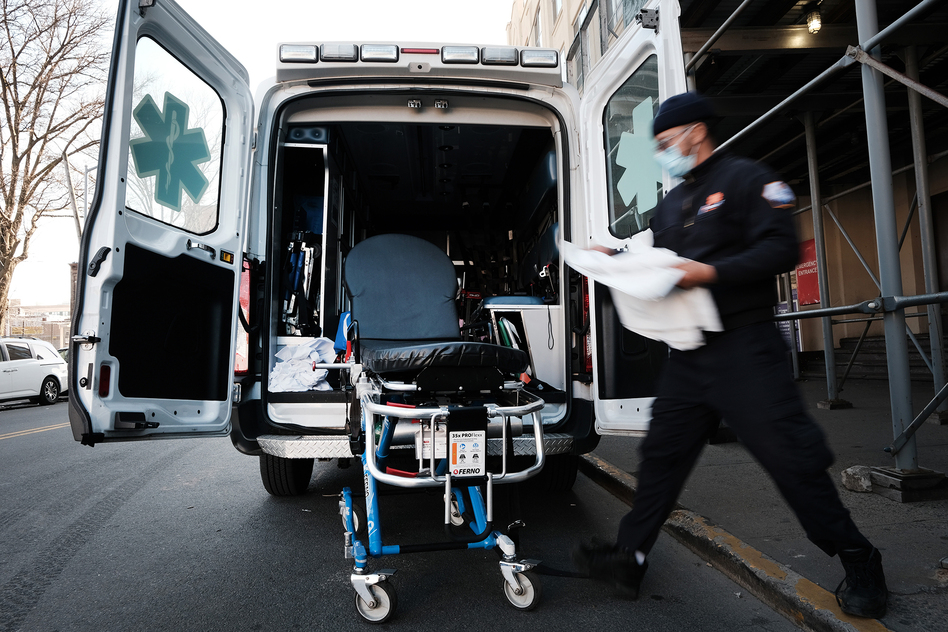 New York City has started the Behavioral Health Emergency Assistance Response Division, or B-HEARD, to provide more targeted care for those struggling with mental health issues. Here in March, an EMT worker cleans a gurney after transporting a suspected COVID-19 patient. (Spencer Platt/Getty Images)