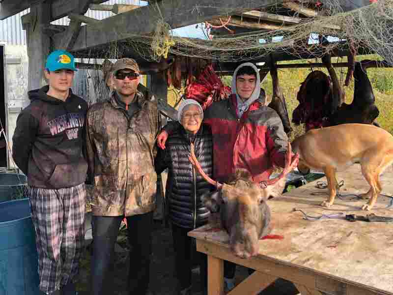Jamin Crow, 18, right, with his brother, father and grandmother (Peter Crow, Jack Crow and Lucy Crow) and a moose they caught that day. The meat will feed their family for four to six months.