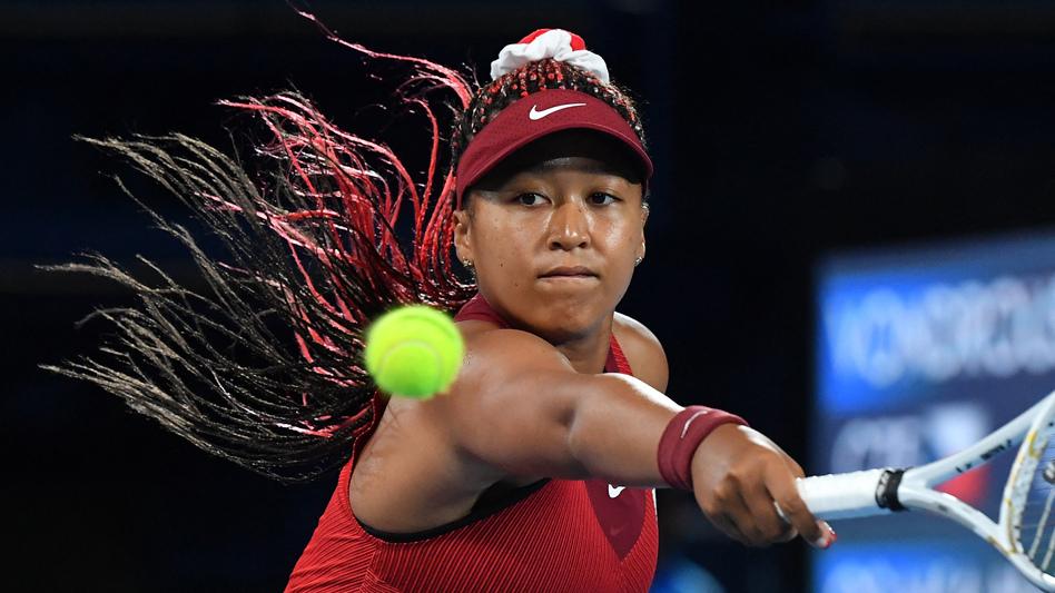 Japan's Naomi Osaka returns the ball to the Czech Republic's Marketa Vondrousova during their third round tennis match at the Tokyo Games on Tuesday. (Tiziana Fabi/AFP via Getty Images)