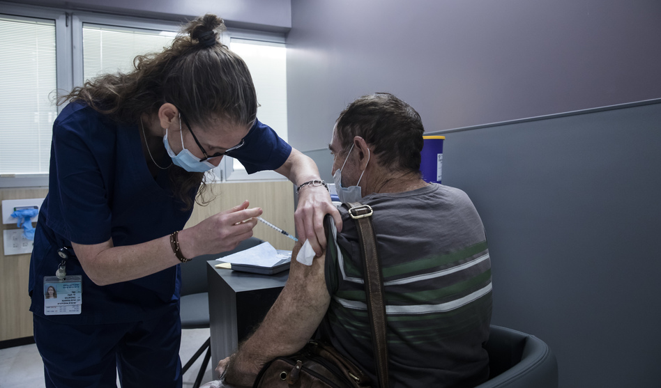 A man receives the Pfizer COVID vaccine in Ramat Gan, Israel. A small Israeli study suggests vaccinated people who experience rare breakthrough infections may develop symptoms that last as long as six weeks. (Amir Levy/Getty Images)