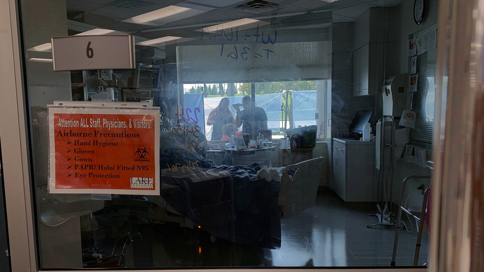 Family members gather outside the window of a COVID-19 patient at Lake Regional Hospital in Osage Beach, Mo., on Monday. (Sarah Blake Morgan/AP)