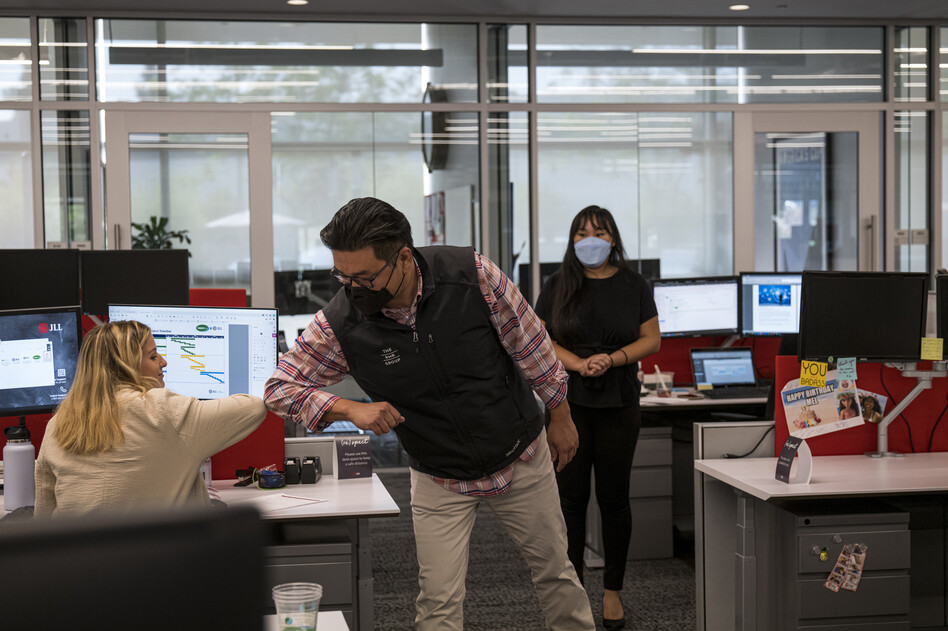 Employees elbow bump at a JLL office in Menlo Park, Calif., in September. With the delta variant surging, mask mandates are returning, and some employers are now requiring employees to be vaccinated before coming to the office. (David Paul Morris/Bloomberg via Getty Images)