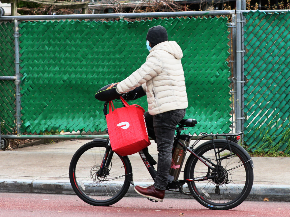 A DoorDash delivery person rides their bike in New York City. Workers across the country went on strike on July 31 to demand higher pay and tip transparency. (Michael M. Santiago/Getty Images)