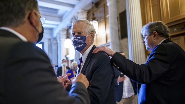 Sen. Angus King, I-Maine, center, speaks with Sen. Gary Peters, D-Mich., left, while Sen. John Kennedy, R-La., walks by at right, as the Senate voted to formally begin debate on a roughly $1 trillion infrastructure plan on Friday.