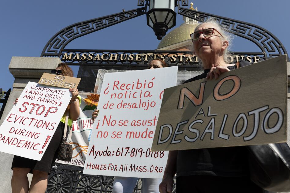 People from a coalition of housing justice groups hold signs protesting evictions during a news conference outside the Statehouse on Friday in Boston. (Michael Dwyer/AP)