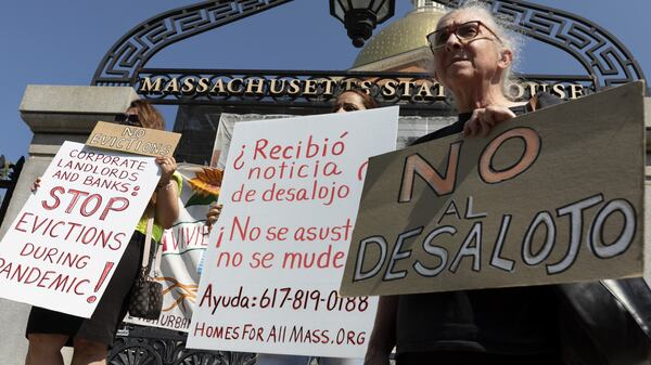 People from a coalition of housing justice groups hold signs protesting evictions during a news conference outside the Statehouse on Friday in Boston.