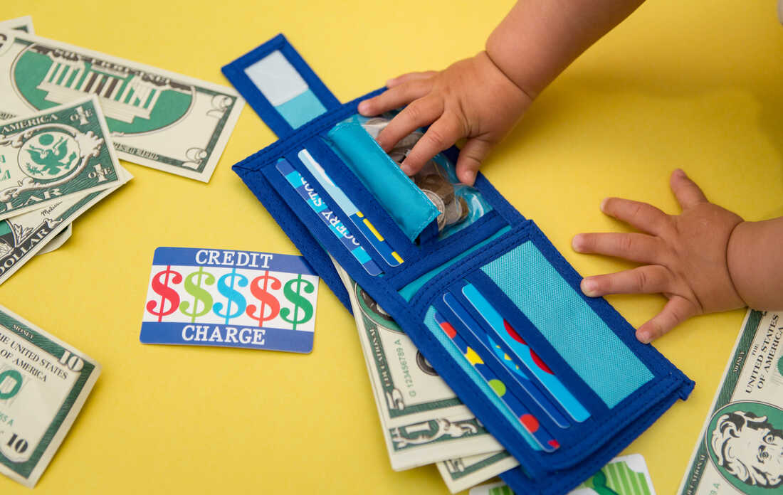 Photograph of a child's hands playing with toy money and a toy wallet full of fake cards, including a toy credit card. The photo is taken from overhead against a yellow backdrop.