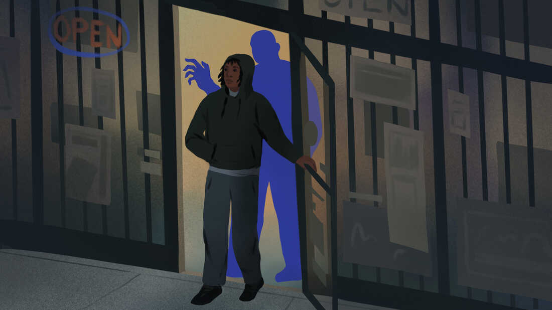 A teenager walks out of a store as a looming blue shape raises his hand behind him.