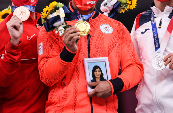 Japan's Ryo Kiyuna holds a portrait of his late mother with his men's kata gold medal at a ceremony in the karate competition.