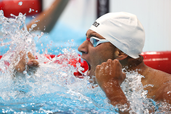Tunisian swimmer Ahmed Hafnaoui celebrates after winning the gold medal in the men's 400 meter freestyle final.