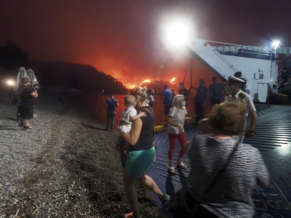 People evacuate from a wildfire north of Athens, Greece, on Friday. A climate-driven heat wave helped create conditions for the fire to burn out of control. Scientists warn that humans are running out of time to curb greenhouse gas emissions and avoid catastrophic global warming. (Thodoris Nikolaou/AP)