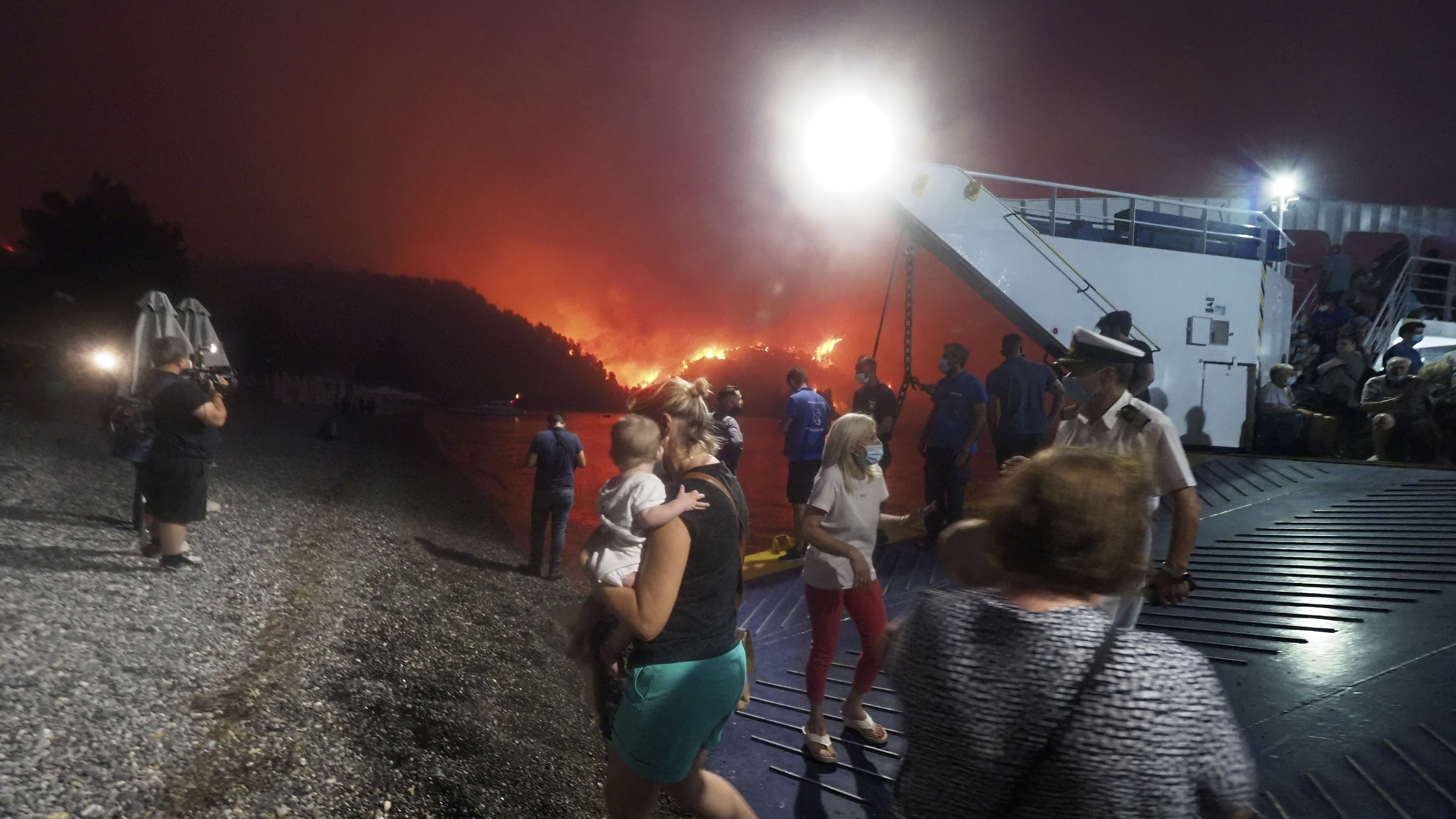 People evacuate from a wildfire north of Athens, Greece, on Friday. A climate-driven heat wave helped create conditions for the fire to burn out of control. Scientists warn that humans are running out of time to curb greenhouse gas emissions and avoid catastrophic global warming.