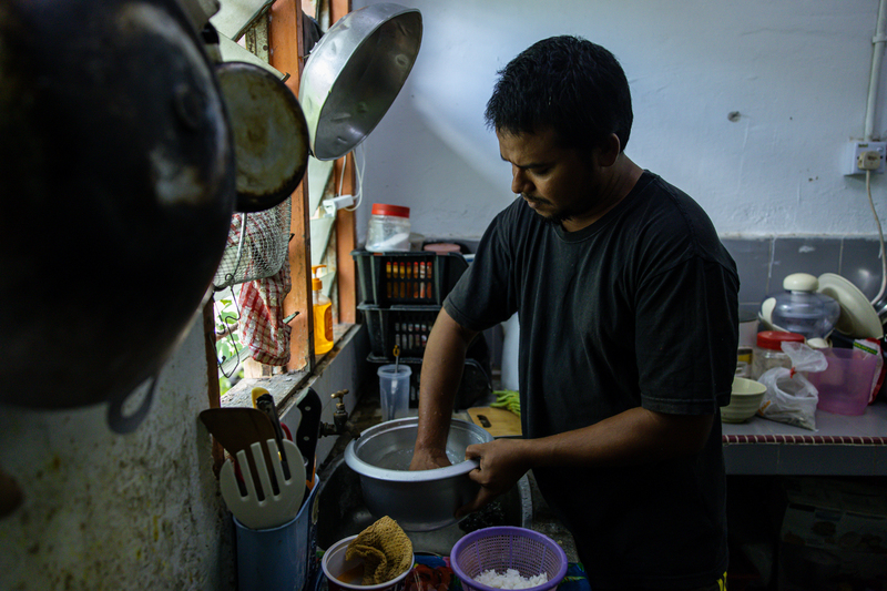 """Mohd, 32, prepares a dish his mother taught him: a mix of rice, lentils, curry, chopped long beans and chili powder. """"Let my wife rest today. I will cook and show you!"""" he says."""