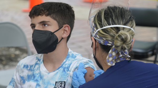 Andres Veloso, 12, gets vaccinated on Monday in Miami. Florida is reporting a surge of COVID-19 cases caused by the highly contagious delta variant.