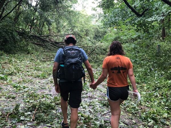 Nick Bergus and his wife Laura Bergus walk hand in hand over tree debris left behind by the derecho near Cedar Rapids, Iowa, on Aug. 10, 2020.