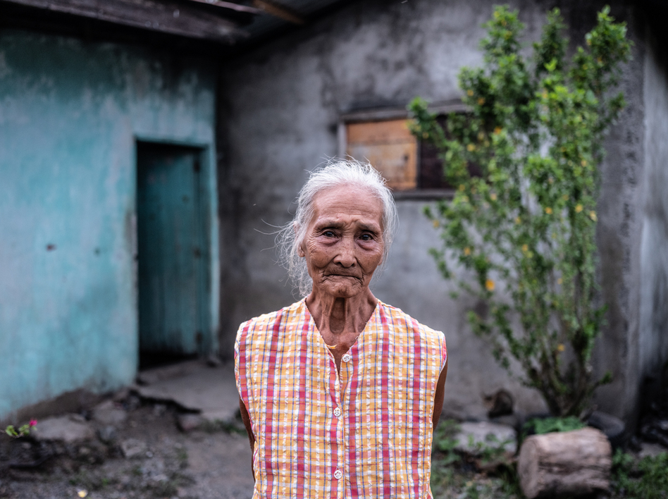 Gloria Hernandez, 82, stands outside her home in Aliaga, a village in the Philippines, where she lives with her daughter and grandsons. During the pandemic, she has been struggling to afford fresh meat and fish. (Xyza Cruz Bacani for NPR)