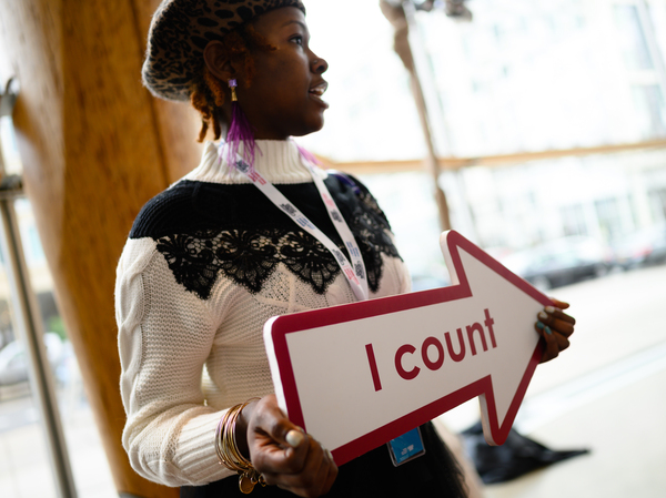 """Whitney Turner, an employee of the U.S. Census Bureau, holds an """"I count"""" sign at a 2020 census advertising campaign event in Washington, D.C., in January 2020."""