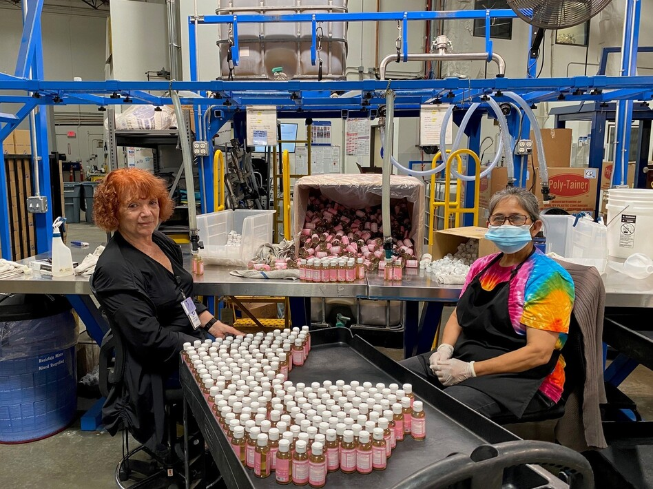 Alice Gomez and Maria Ramos work at Dr. Bronner's soap factory in Vista, Calif. The company is doing weekly coronavirus testing but still wants all its workers vaccinated. (Andrea Hsu/NPR)