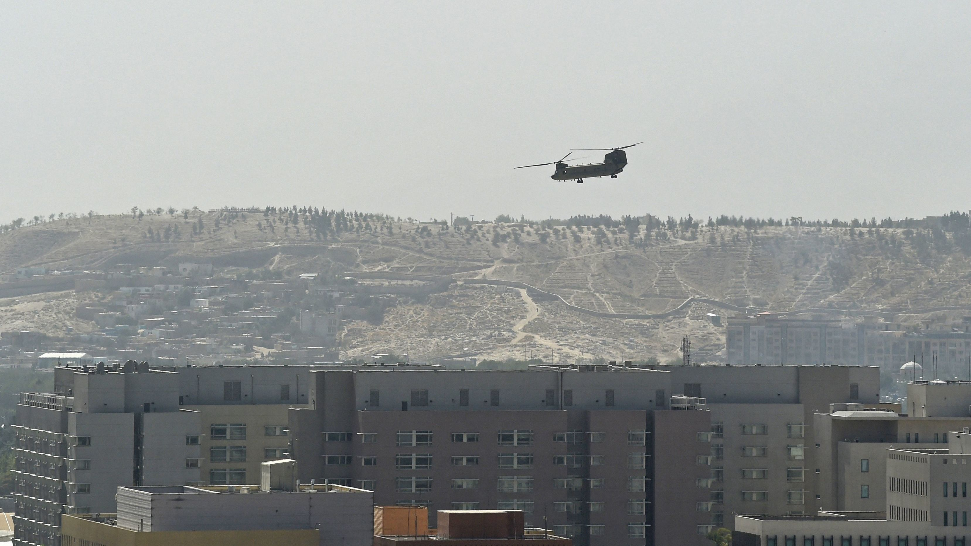 A U.S. military helicopter is pictured flying above the U.S. Embassy in Kabul on Sunday. The Taliban swept into Kabul, facing little resistance.