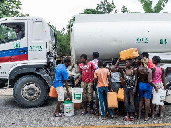 People gather near bins of water in Camp-Perrin, Haiti, on Monday.