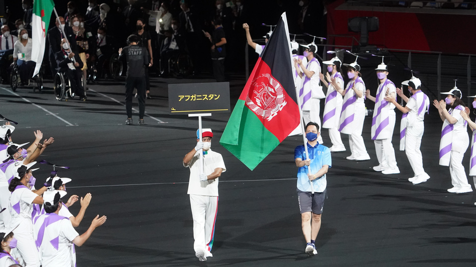 The flag of Afghanistan is presented by volunteers at the Paralympics.