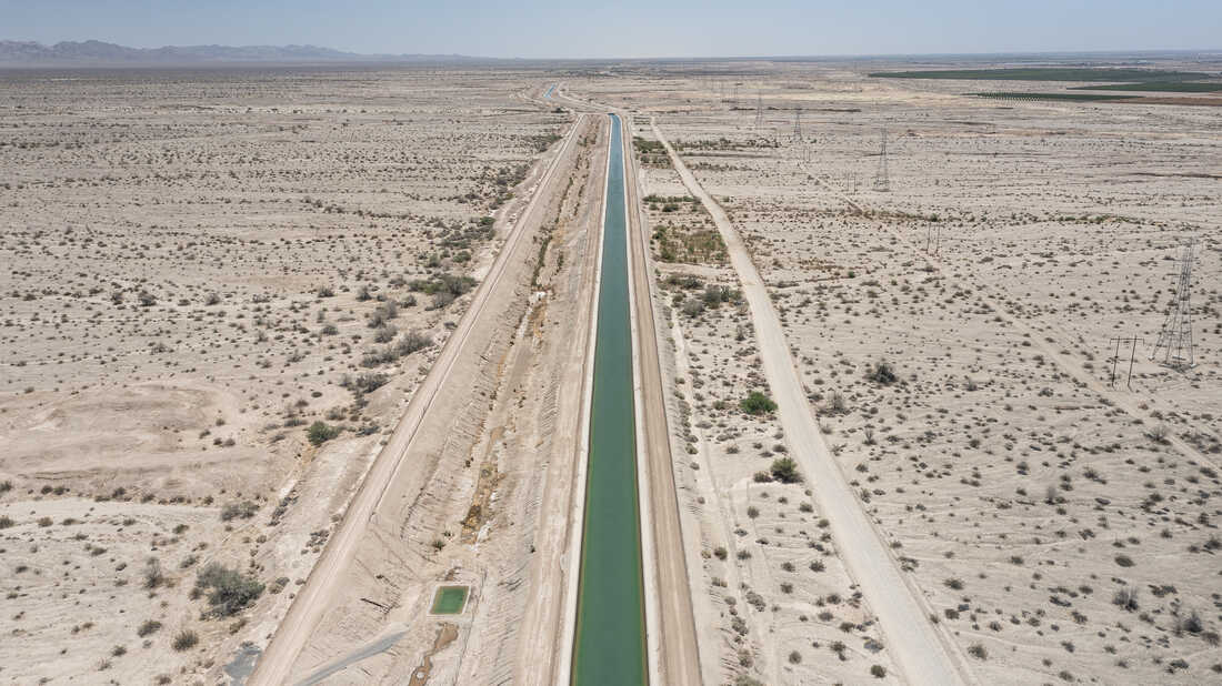 An irrigation canal in the Southern California desert carries water to agricultural fields growing crops in the desert region near the Salton Sea.