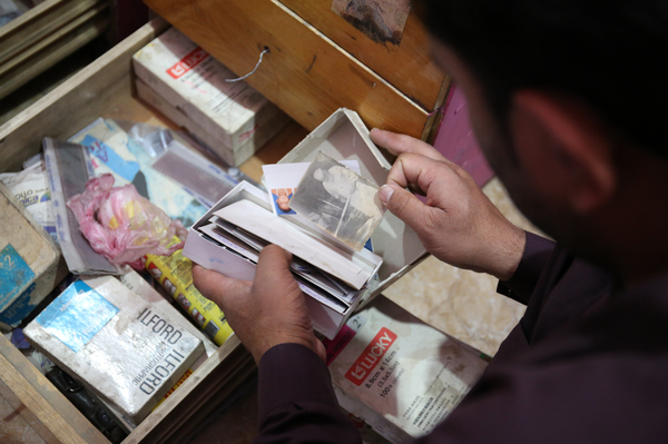 A photo studio owner rummages through boxes of uncollected or duplicate photographs in a dusty backroom.