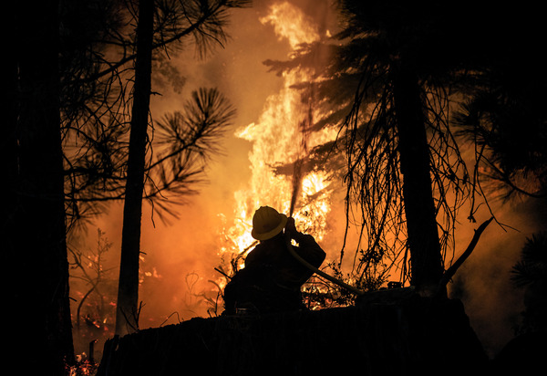 A firefighter with the U.S. Forest Service battles the advancing Caldor Fire on Aug. 28 in Strawberry, Calif.