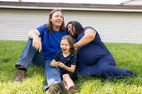 Mat Pergens rests on the grass outside his apartment with his wife, Amanda, and daughter Sylvia. What he really wants is a yard of his own.