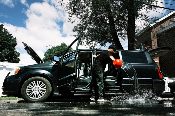A teenager dumps out water from a car in a flooded Queens neighborhood on Friday. Across the Northeast, people are cleaning up from Ira's wrath.
