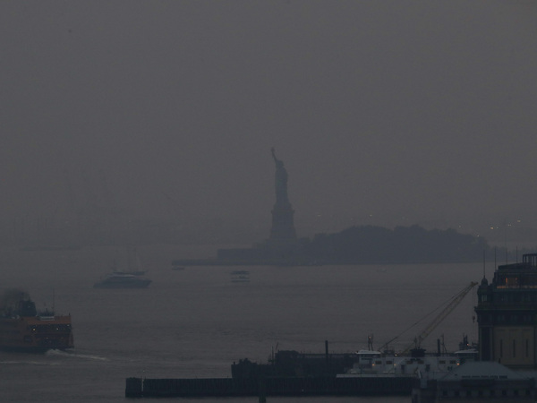 The Staten Island Ferry departs from the Manhattan terminal through a haze of smoke from Western wildfires with the Statue of Liberty barely visible on Tuesday July 20 2021
