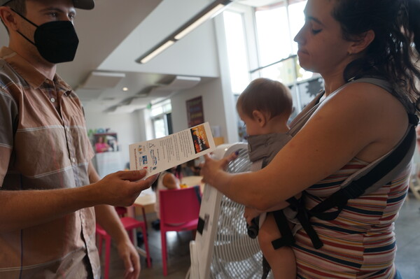 Mason Dow a member of Climate Smart Missoula gives a free air filter to a new mother at a local food bank explaining the impacts of wildfire smoke on human health