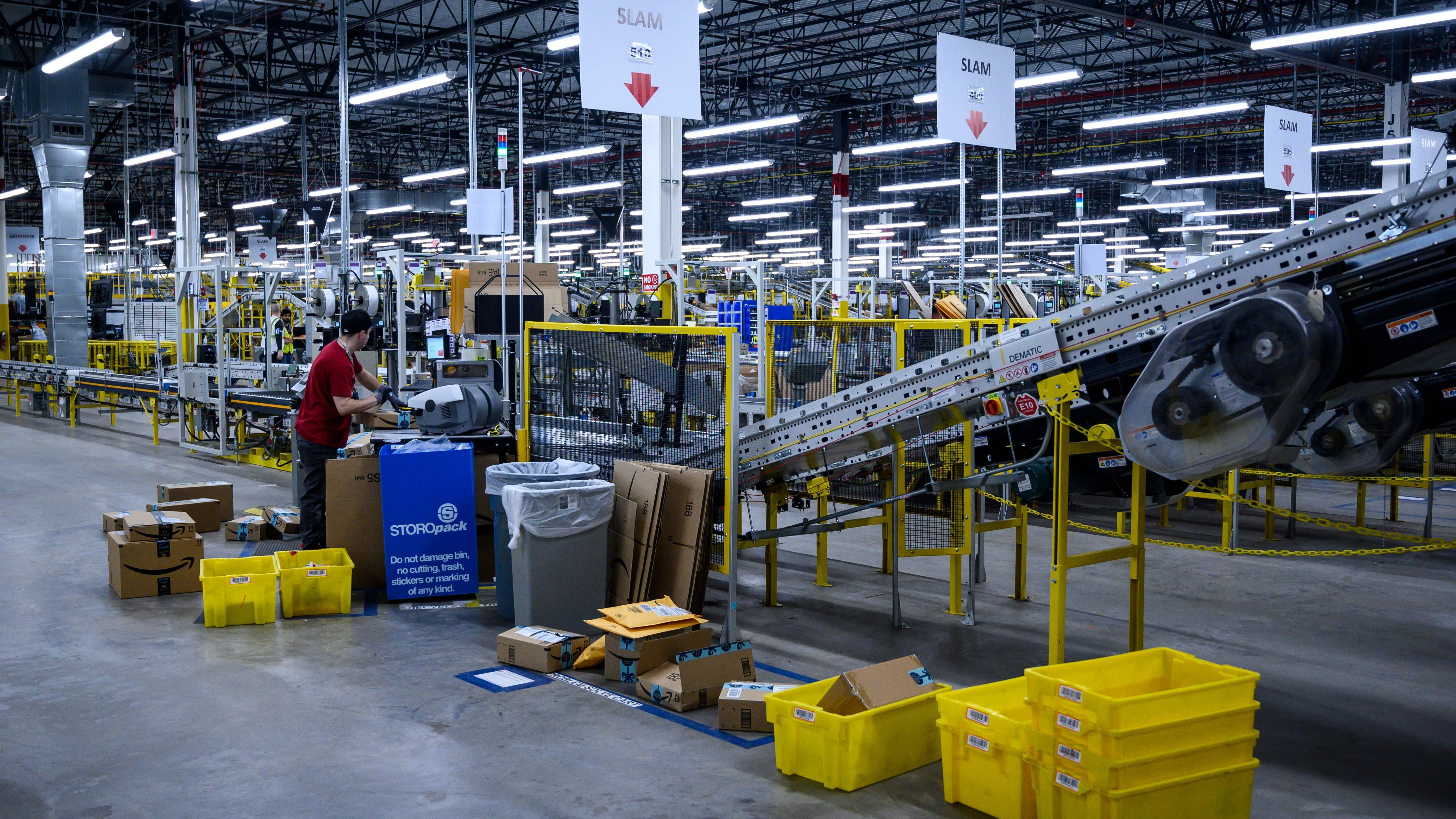 A man works at a conveyor belt at an Amazon warehouse in New York City in 2019.
