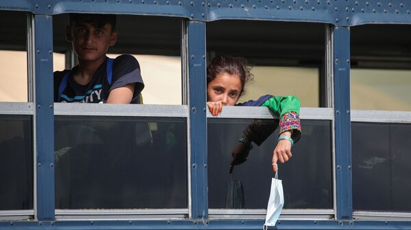 Afghan evacuees sit on a bus at the U.S. air base in Ramstein, Germany, on Aug. 26. Ramstein Air Base, the largest U.S. Air Force base in Europe, has hosted thousands of Afghans.