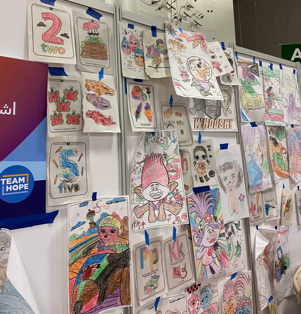 At the Dulles Expo Center in Virginia, a special corner is reserved just for kids, where they can play, color and draw with crayons and pads, supervised by aid workers from the humanitarian organization Save the Children.