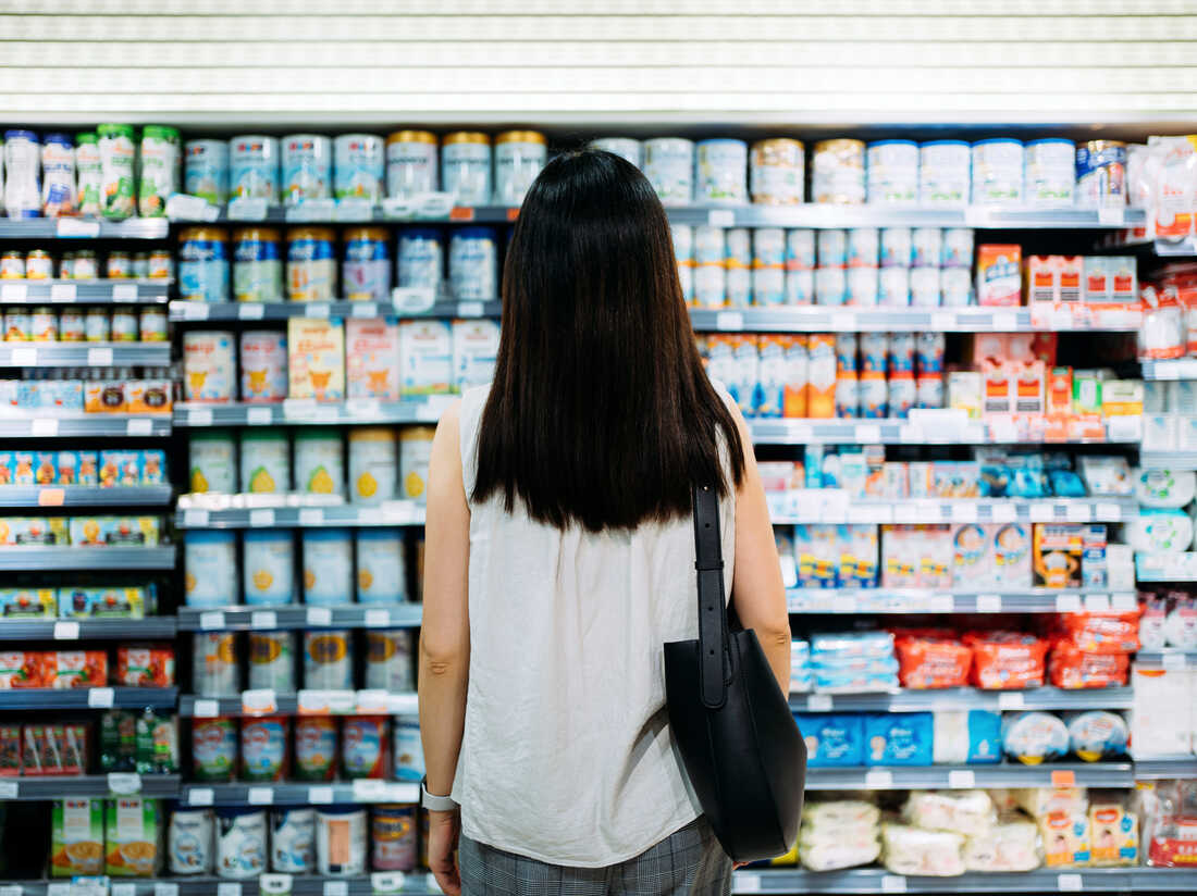 Rear view of young Asian mother groceries shopping for baby products in a supermarket. She is standing in front of the baby product aisle and have no idea which product to choose from