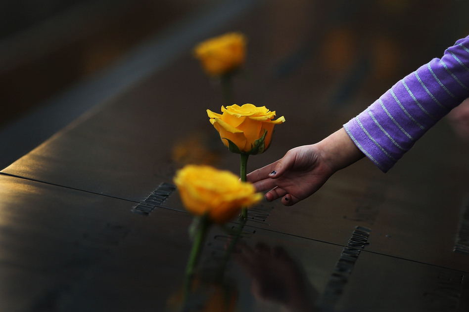 A child reaches out to touch a flower adorning the Sept. 11 memorial on the name of a veteran killed in the 2001 terror attacks. For today's generation of kids, 9/11 is a history lesson.