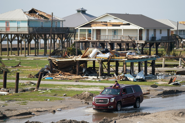On Sept. 3, a motorist drives past houses damaged by Hurricane Ida in Grand Isle, La. Ida made landfall as a Category 4 hurricane, causing flooding, wind damage and power outages along the Gulf Coast.