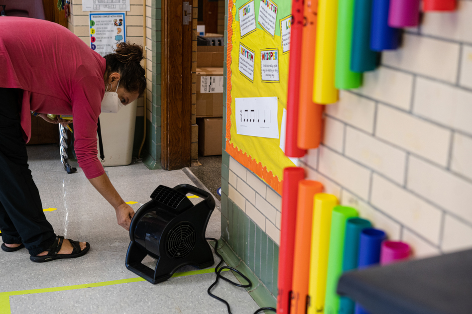 Quesada turns on a fan outside her classroom door. She spends most of her time before class on COVID-19 precautions. She has spent nearly $600 of her own money on air purifiers and fans to improve the ventilation in her classroom.