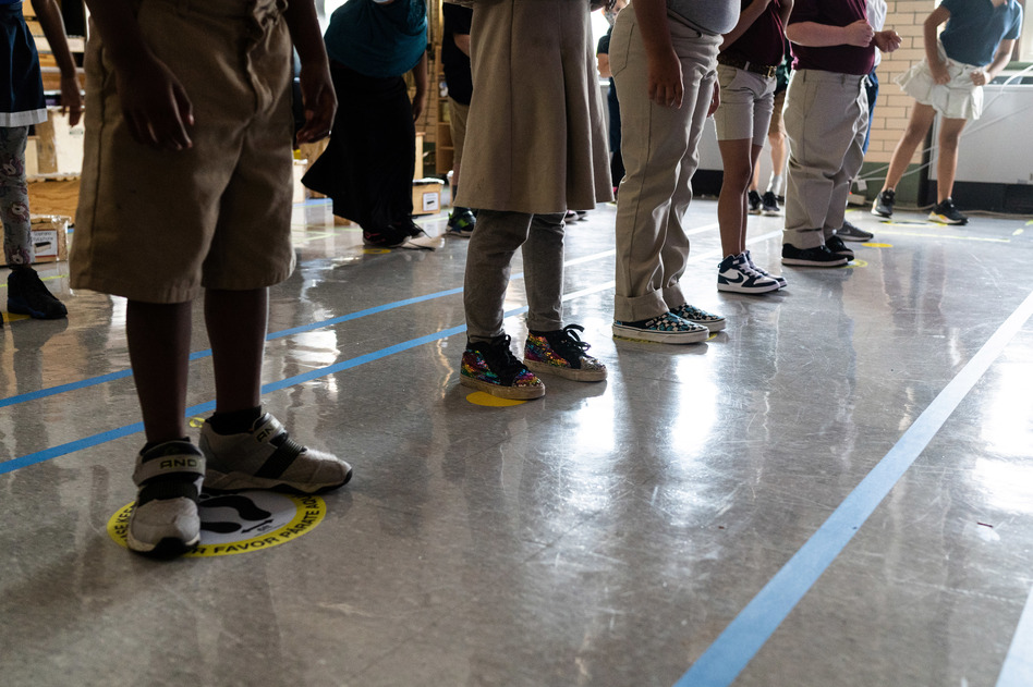 In order to keep them as separated as possible, students in Quesada's third grade class stand on carefully placed stickers on the floor. Because of the space instruments take up, and the need for students to be able to see their teacher, there's often only room for children to stand 3 feet apart, instead of 6.