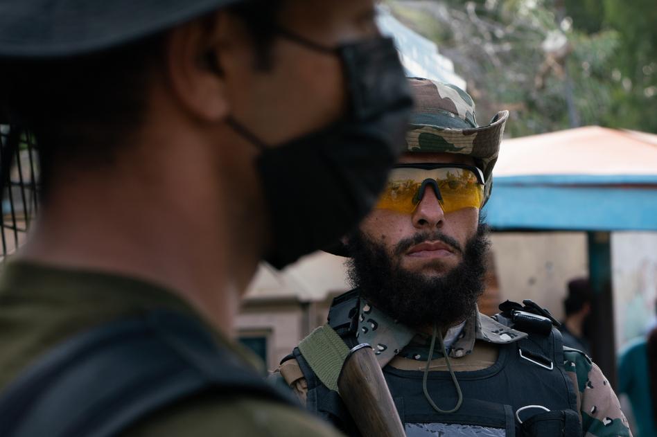 A Taliban guard (right) stands adjacent to a Pakistani guard at the Torkham border crossing.