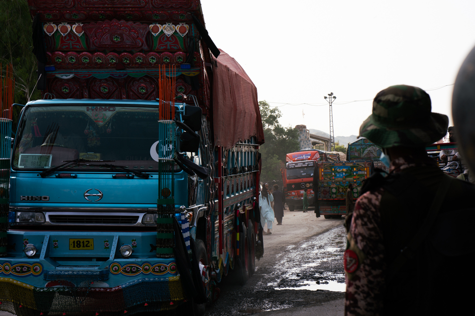A brightly painted truck passes through Torkham while a Pakistani guard watches.