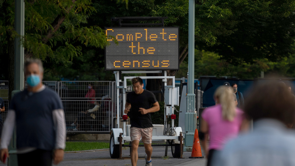 """People pass by a """"Complete the census"""" sign along New York City's Hudson River Greenway in September 2020. (Alexi Rosenfeld/Getty Images)"""