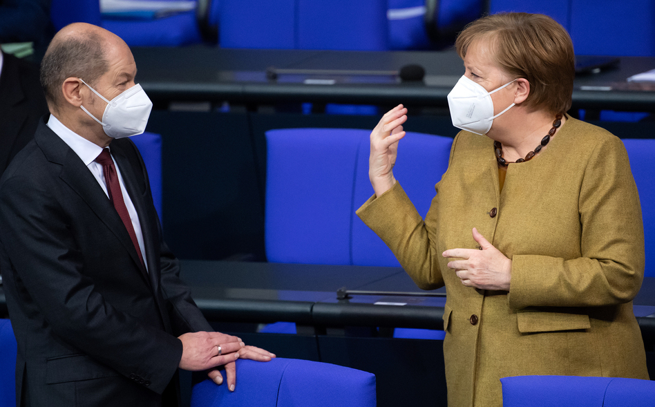 Olaf Scholz, Germany's finance minister, and Chancellor Angela Merkel talk at the beginning of the plenary session in the German parliament, the Bundestag, in Berlin on Jan. 28.