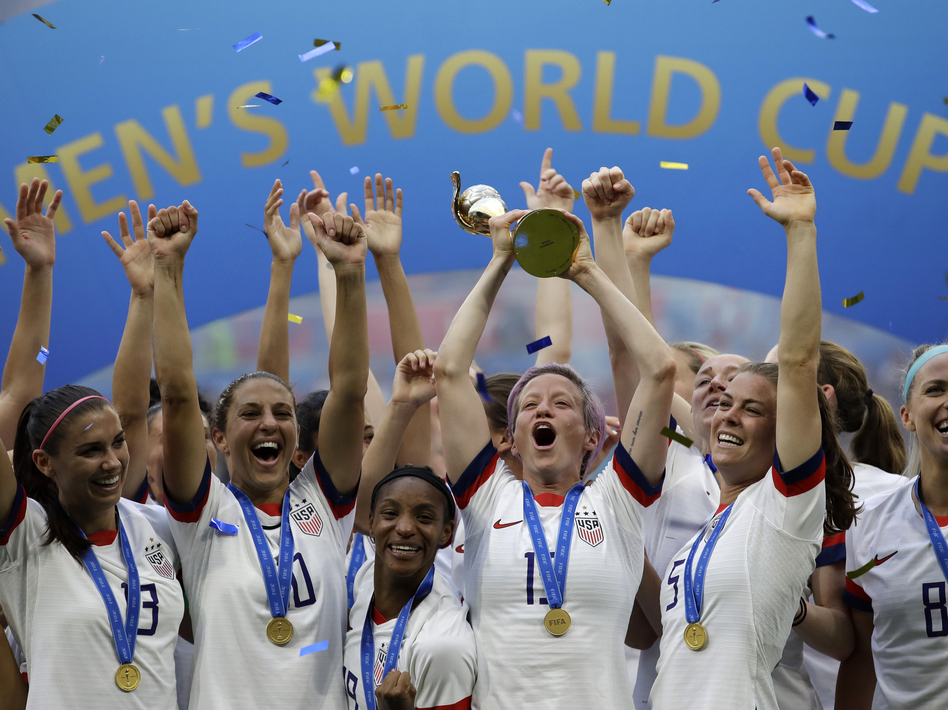 U.S. soccer player Megan Rapinoe raises the trophy in 2019 after winning the Women's World Cup final between the U.S. and The Netherlands in Decines, outside Lyon, France. (Alessandra Tarantino/AP)
