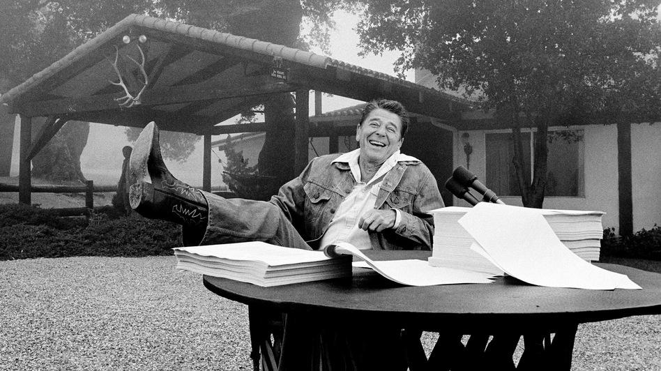 President Ronald Reagan shows his boot following the signing of his tax bill in August 1981 at his vacation home near Santa Barbara, Calif.