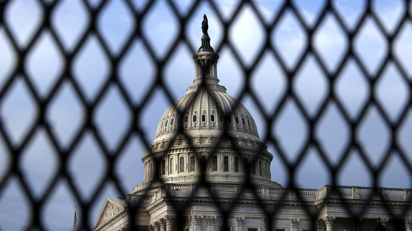 The U.S. Capitol Dome is seen through security fencing in May. Similar barriers will be in place on Saturday, when a demonstration is planned in support of people charged for the Jan. 6 pro-Trump attack on the Capitol.