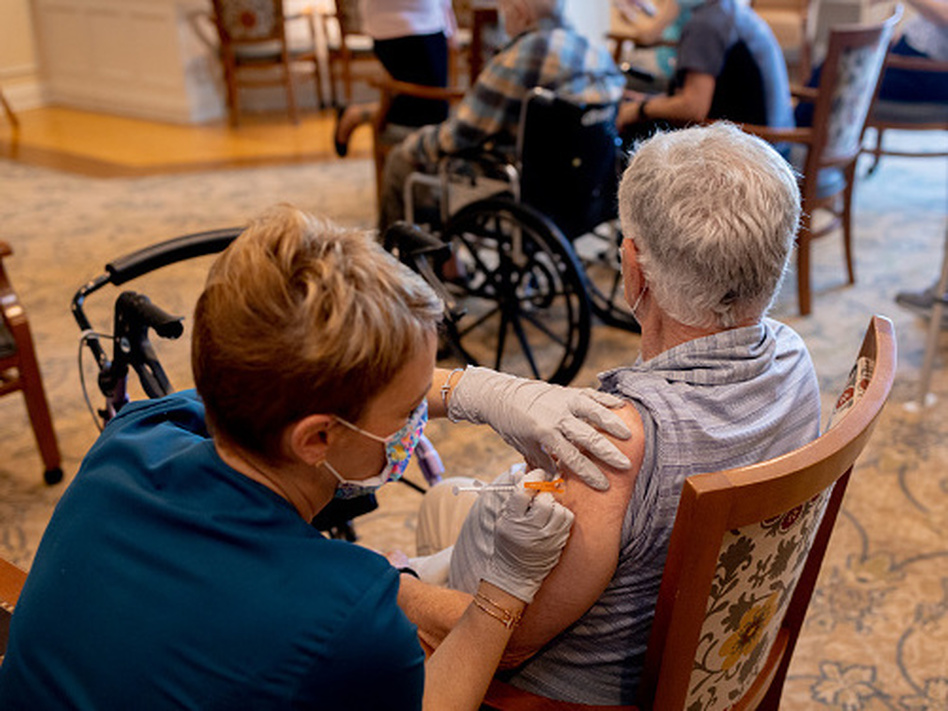 A health care worker administers a third dose of the Pfizer-BioNTech COVID-19 vaccine at a senior living facility in Worcester, Pa., in August. (Hannah Beier/Bloomberg via Getty Images)